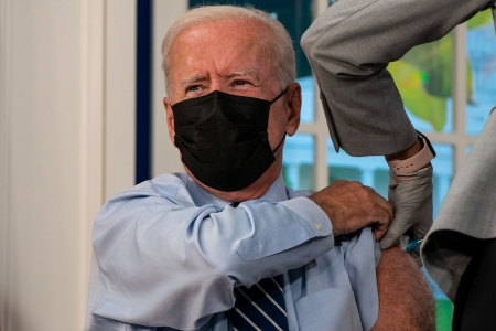 A masked President Joe Biden lifts his sleeve as he gets his booster shot, revealing a very hairy arm.
