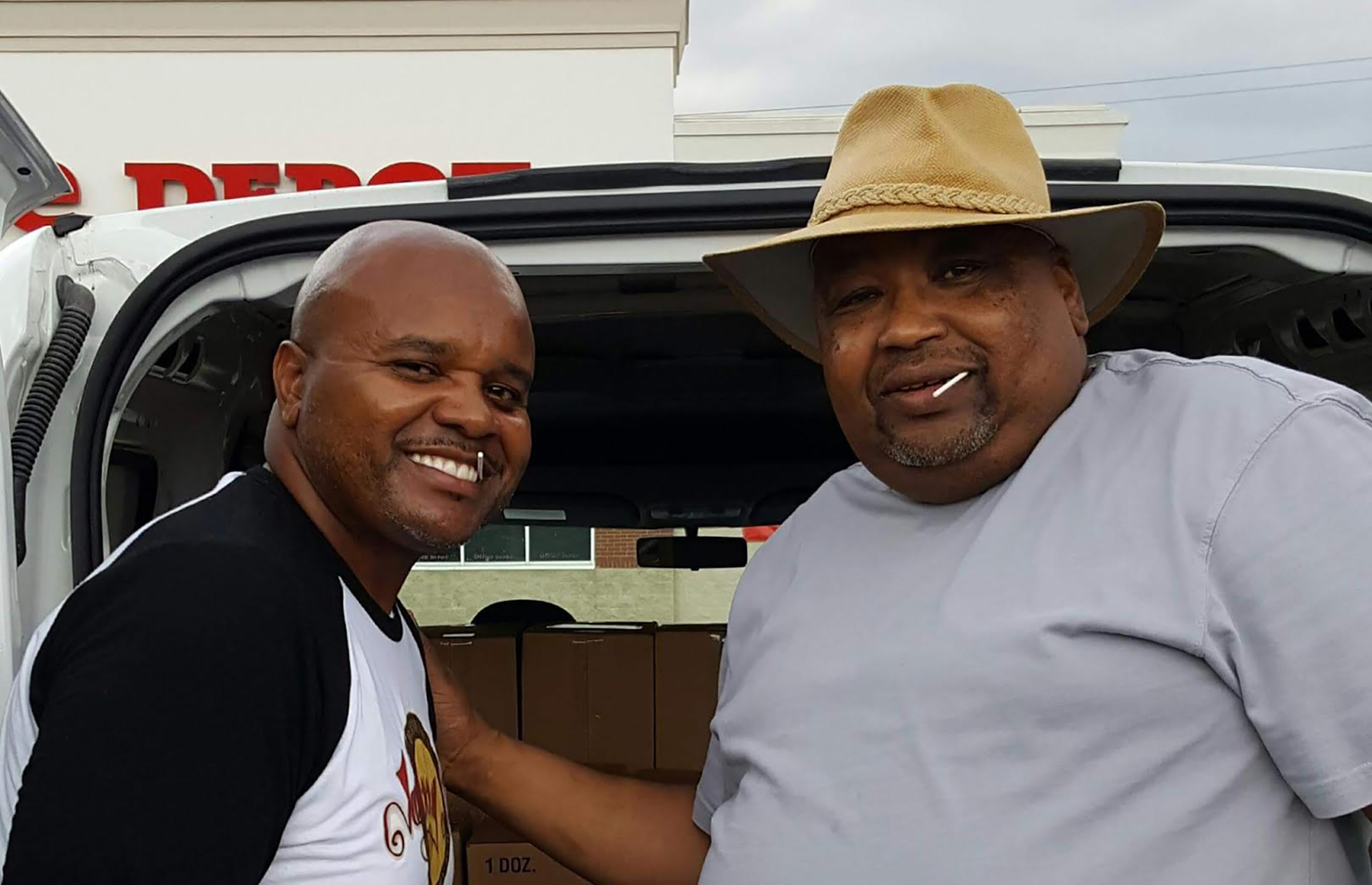 John Perkins of Johnny B's and his father who started the family's successful barbecue joint stand in front of a van.