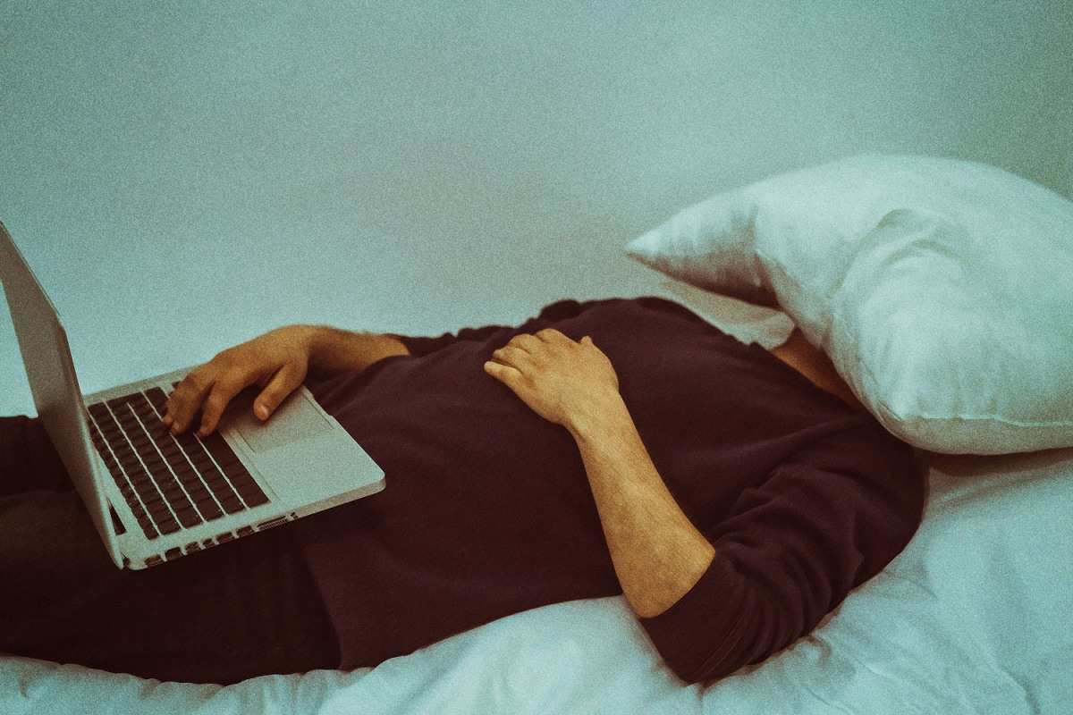 A man sleeps with a pillow on his face and a computer on his lap.