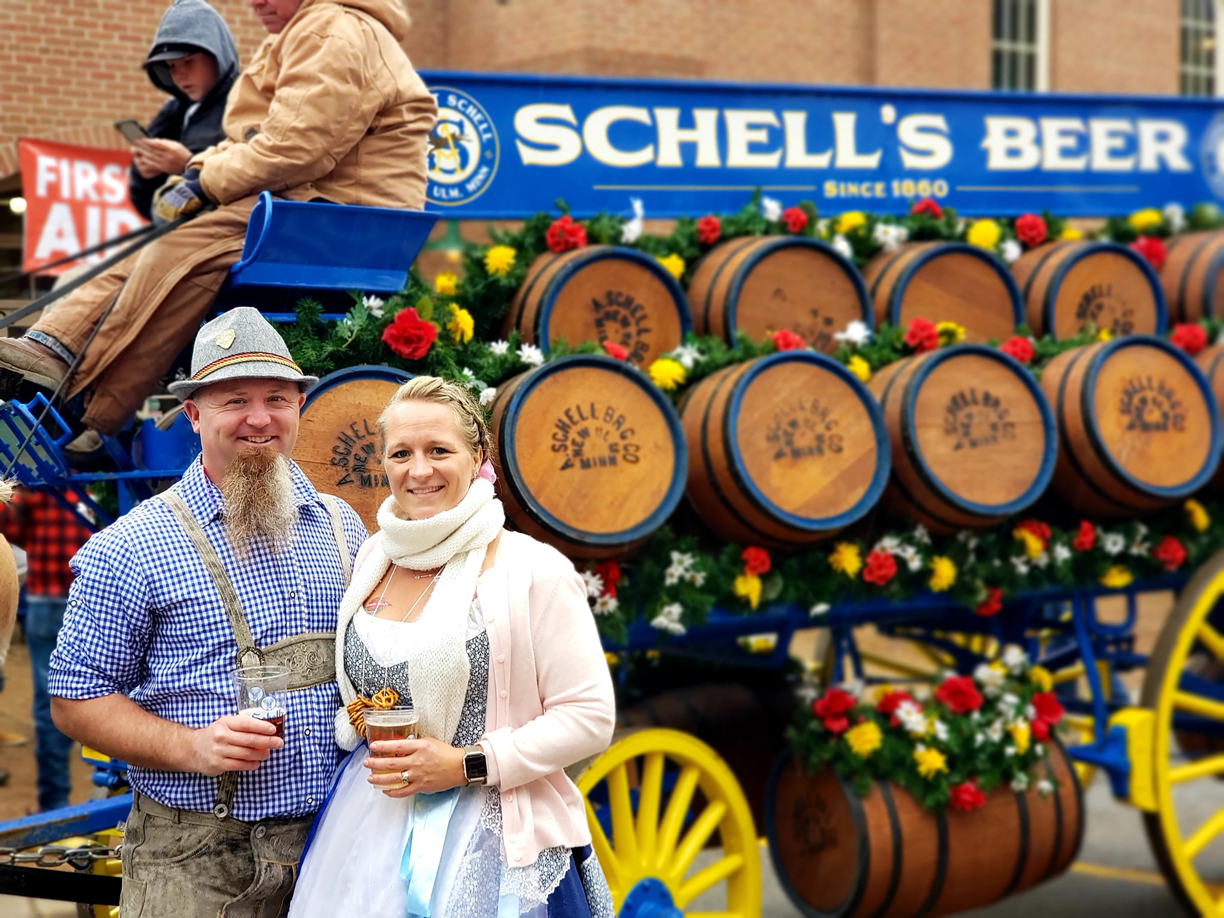 A couple drinks beer in front of Schell's Beer at Oktoberfest in New Ulm.
