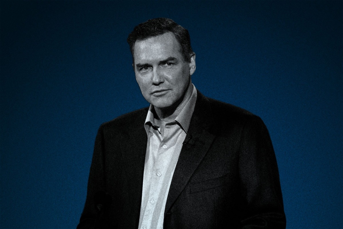 Comedian Norm MacDonald in a blazer and button-up shirt. MacDonald passed away this week at 61.