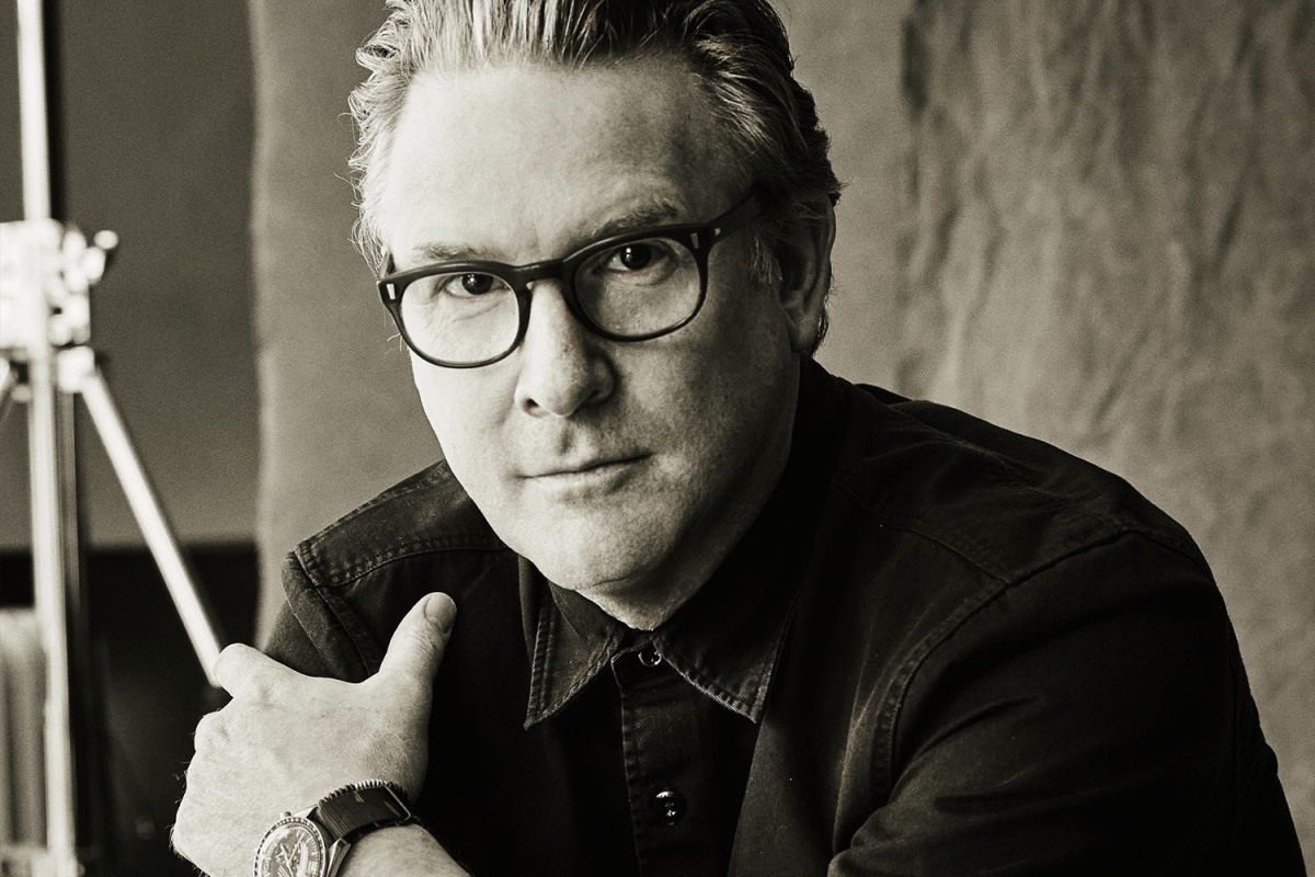 A portrait of menswear designer Todd Snyder, wearing glasses, a watch and a button-up shirt, on the occasion of the 10-year anniversary of his eponymous brand