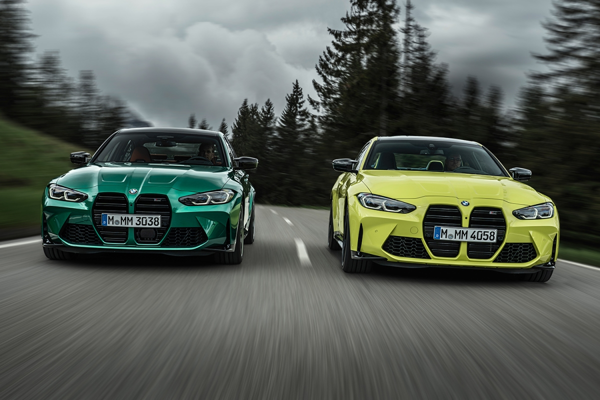 A green 2021 BMW M3 Competition Sedan on the left driving fast next to a 2021 BMW M4 Competition Coupe in yellow on the right with trees looming in the background