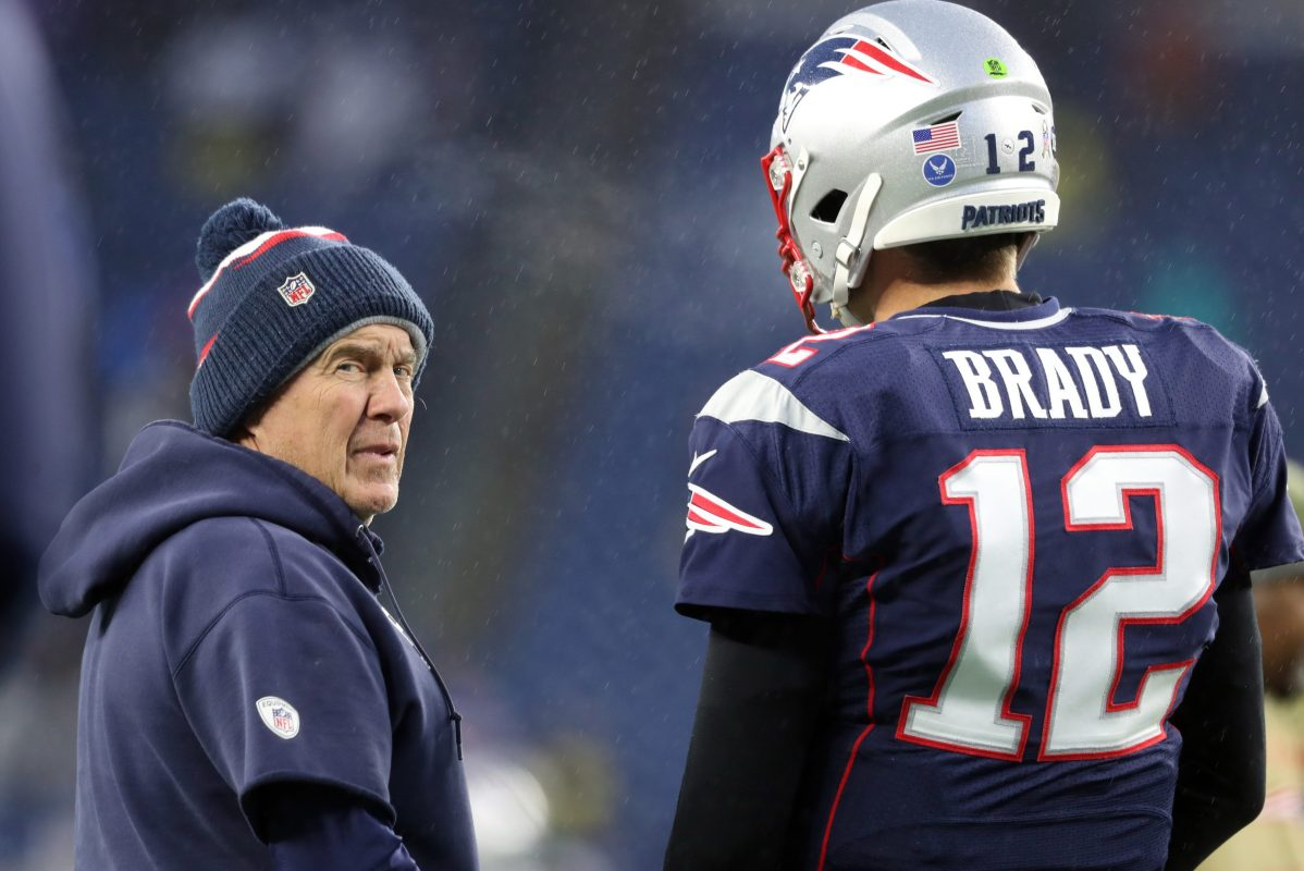 New England Patriots head coach Bill Belichick in a beanie and Tom Brady in full uniform with a helmet talk on the NFL field in 2019