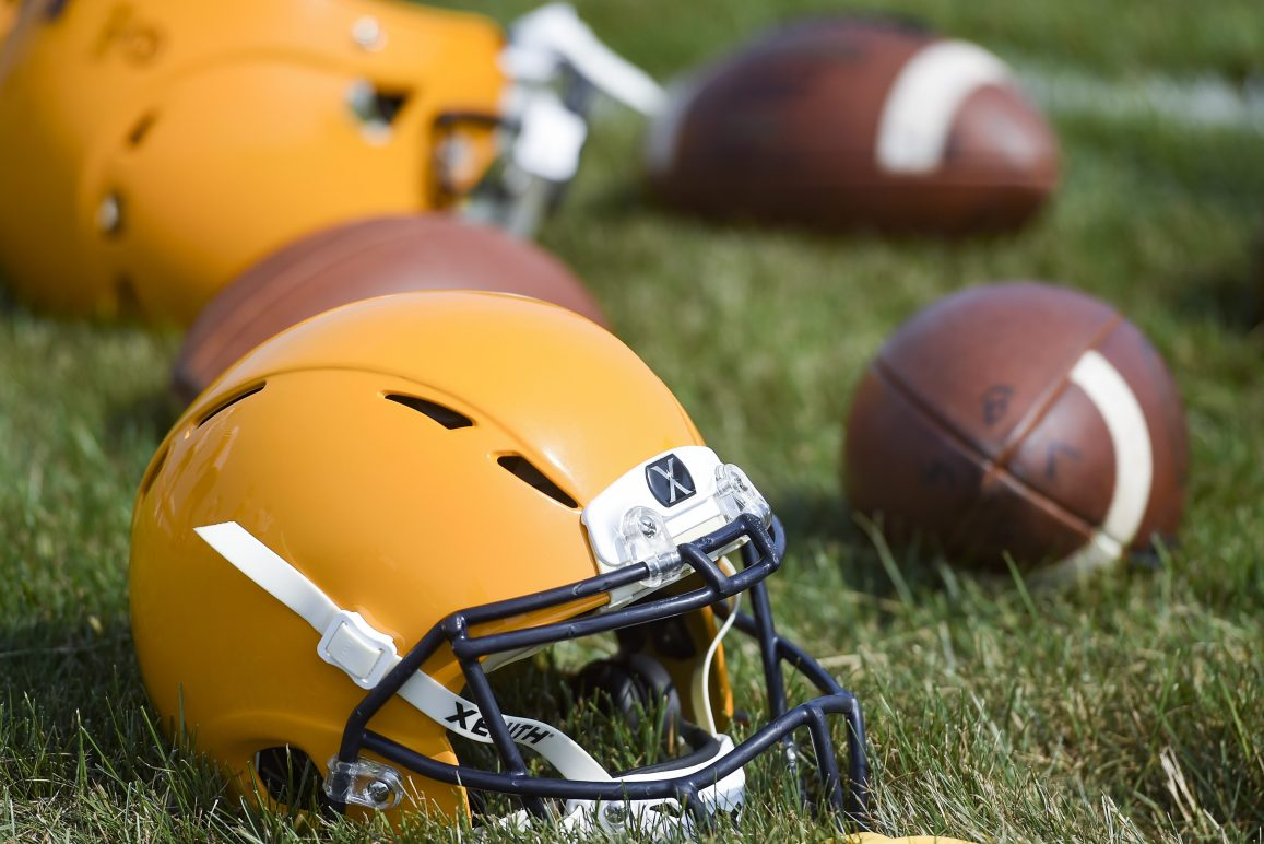 Football helmets and balls on the ground during a high school practice