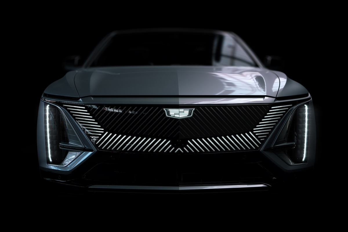 The front end of the new 2023 Cadillac Lyriq, the GM brand's first all-electric SUV, in a black room