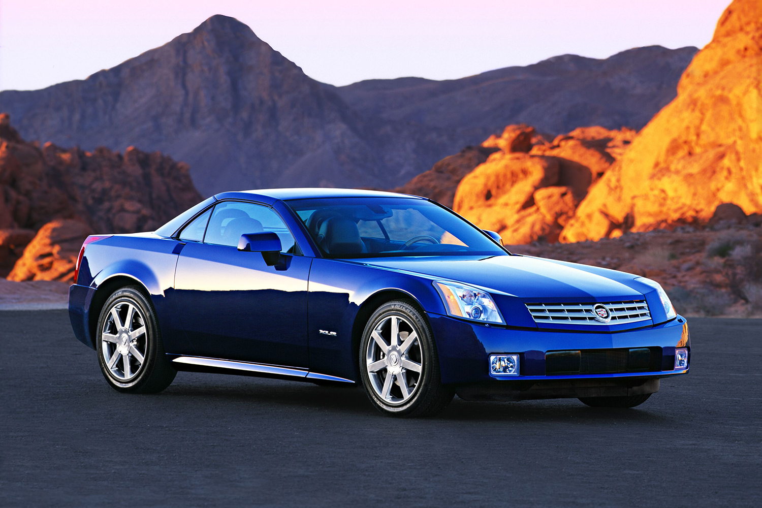 The ill-fated 2004 Cadillac XLR sitting still on the concrete at sunset with desert hills in the background