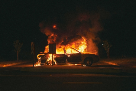 A four-door car on fire in a parking lot at night, with black smoke billowing up into the night sky