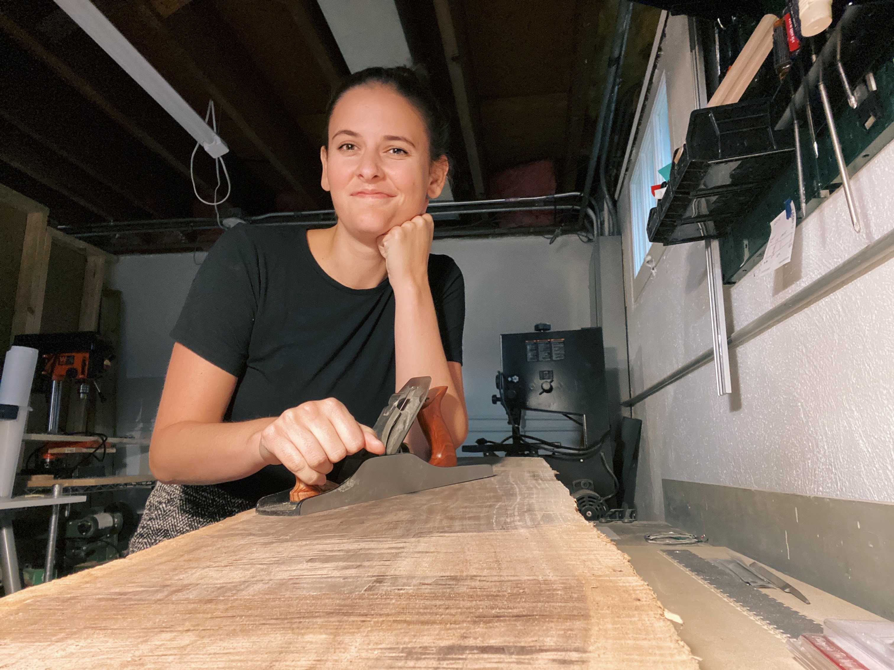 writer claire young hand-planes a piece of black walnut wood at her home in chicago