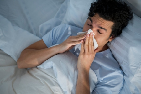 Man in bed blowing nose into tissue