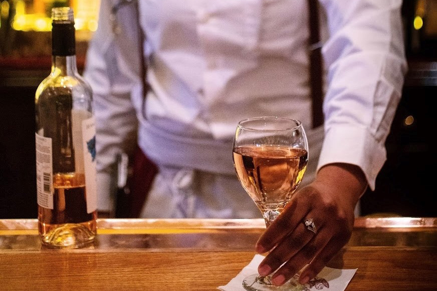 A bartender serves a glass of rosé at the Old Ebitt Grill in DC
