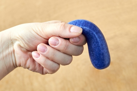 A toy made of plasticine in the hand of a woman, the theme of sexual dysfunctions, the toy symbolizes the penis. Covid-19 may be causing impotence.