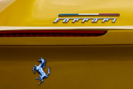 """The words """"Ferrari"""" and the luxury car brand's Prancing Horse logo on a yellow car"""
