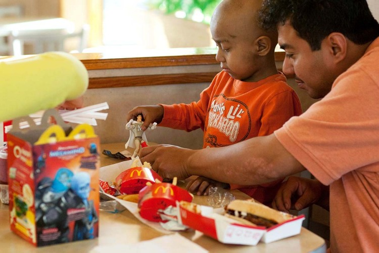 Five-year-old Andy Villatoro plays with a toy he received after ordering a Happy Meal at McDonald's as his father Carlos Villatoro (R) watches on November 3, 2010 in San Francisco, California. McDonald's is now switching away from plastic to more eco-friendly materials for toys in their Happy Meals.