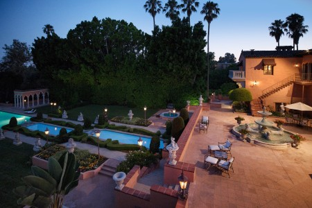 The terrace of the Hearst Estate at sunset featuring a fountain, multiple pools and lush greenery with palm trees in the background against a blue sky