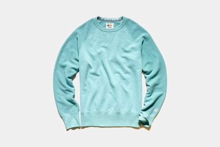 A light blue Todd Snyder sweatshirt against a grey background.