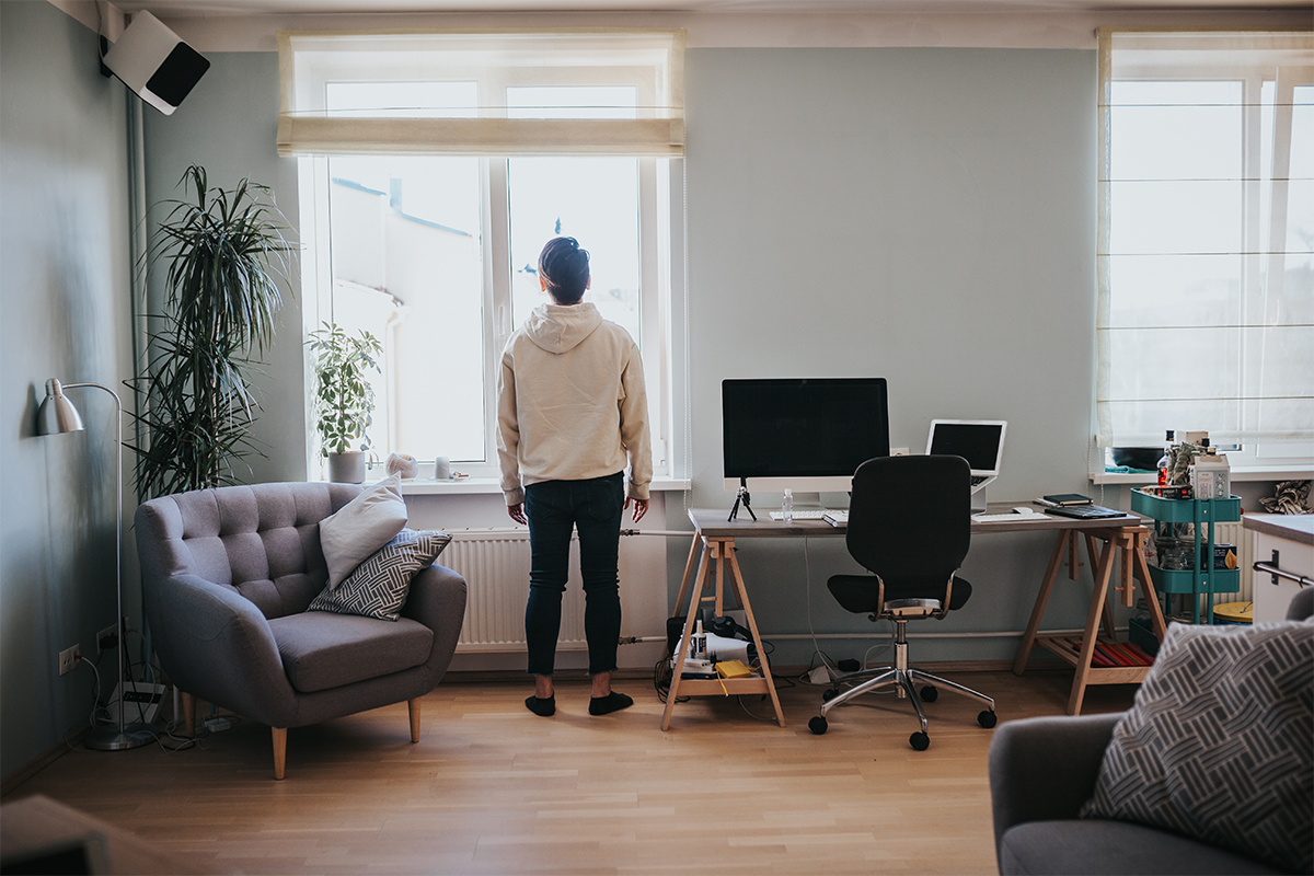 A remote worker takes a break to stare out the window.