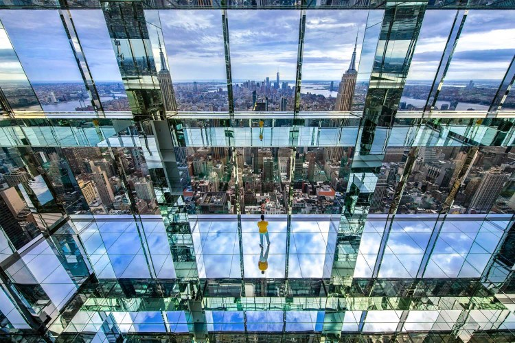 A man looking out onto the downtown Manhattan skyline at SUMMIT One Vanderbilt's mirror room.