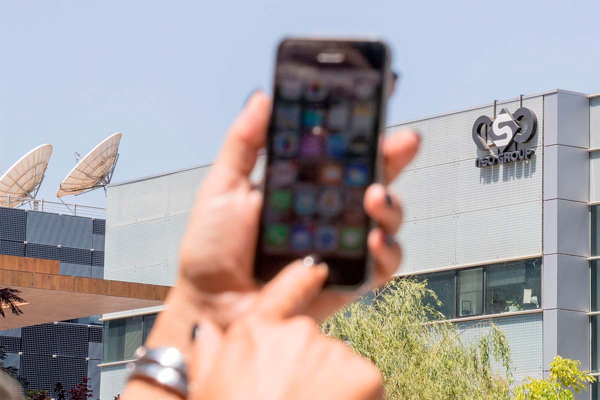 An Israeli woman uses her iPhone in front of the building housing the Israeli NSO group, on August 28, 2016, in Herzliya, near Tel Aviv. NSO's spyware has been an issue for Apple since 2016.