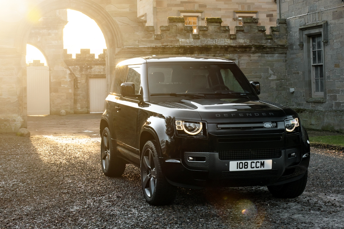 A V8 Carpathian Edition Land Rover Defender SUV in black sitting in the courtyard of a castle in the UK while the sun sets in the background behind the stone walls