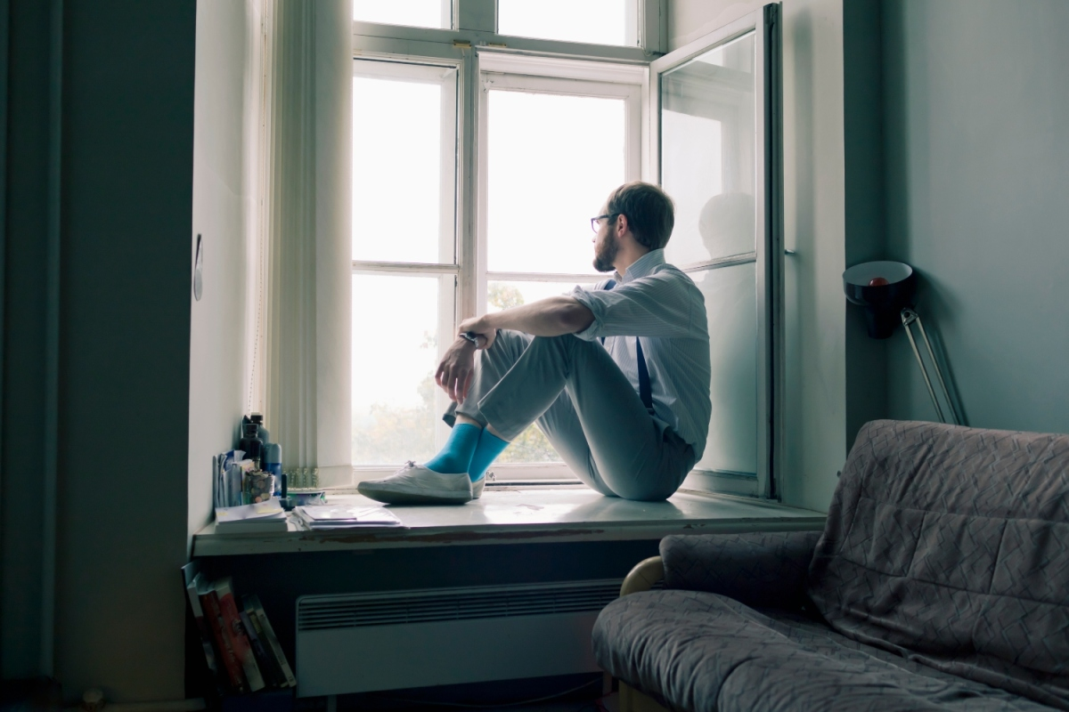 Lonely man sits on window sill gazing out the window