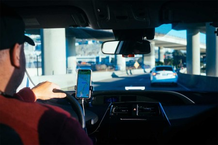 A Lyft driver in his car reading directions from his phone screen