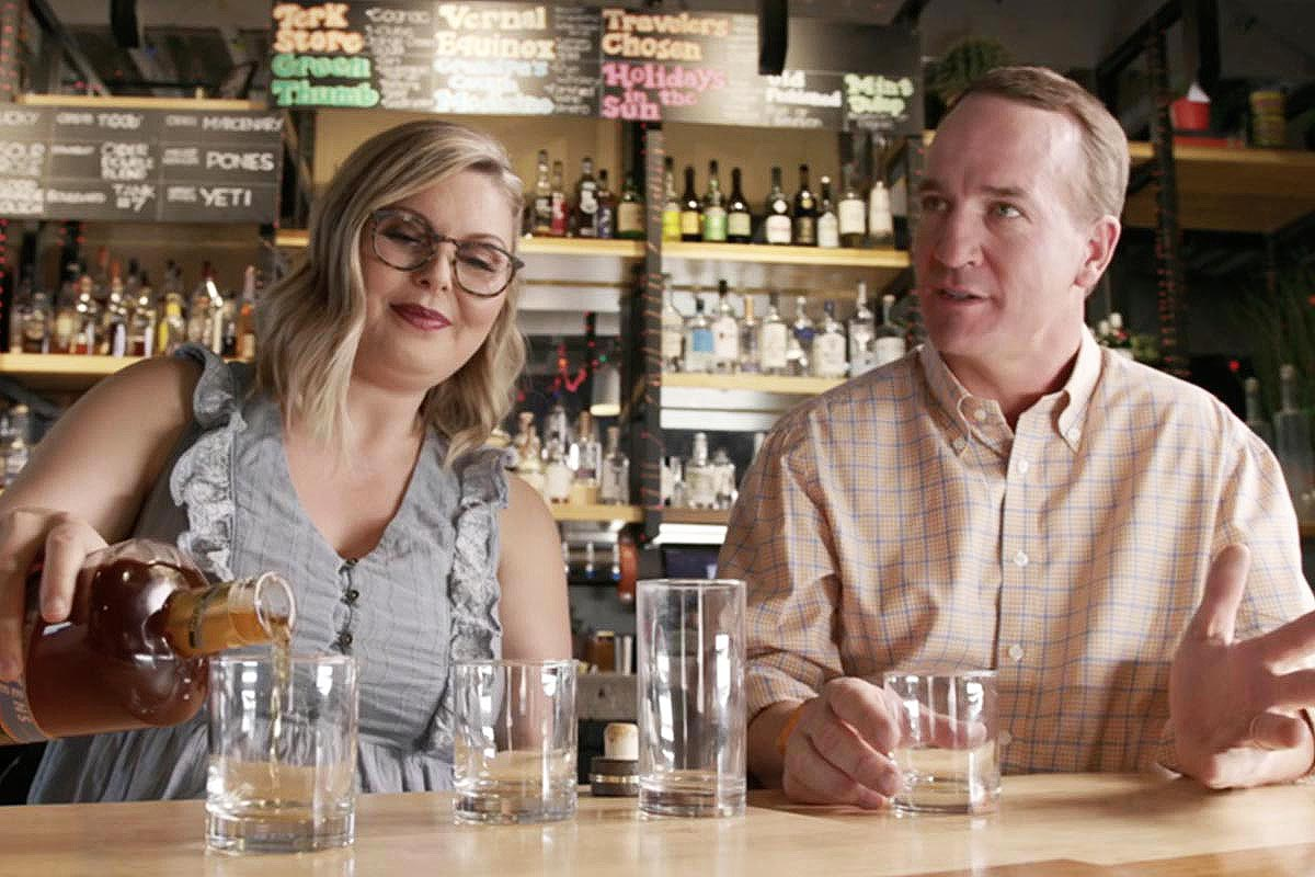 Master Distiller Marianne Eaves and Peyton Manning with a bottle of Sweetens Cove bourbon (which Manning co-owns)