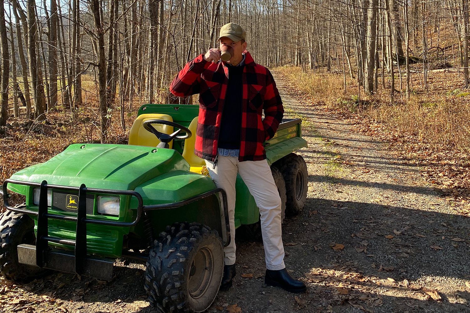 Photographer and magazine editor Matt Hranek sipping a cup of coffee in a buffalo plaid Woolrich jacket standing next to his John Deere Gator utility vehicle in the woods at his upstate New York estate