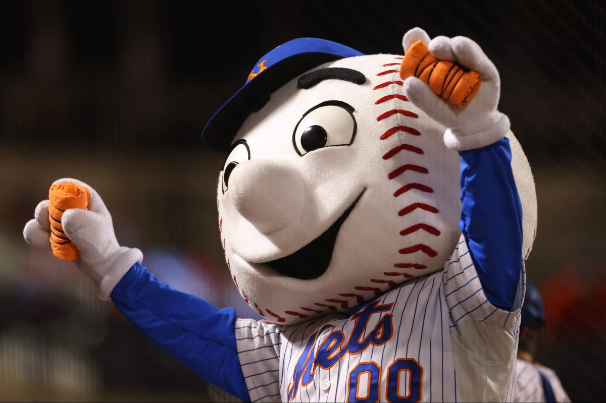 The mascot Mr. Met at a game between the Pirates and Mets at Citi Field with his hands up in the air