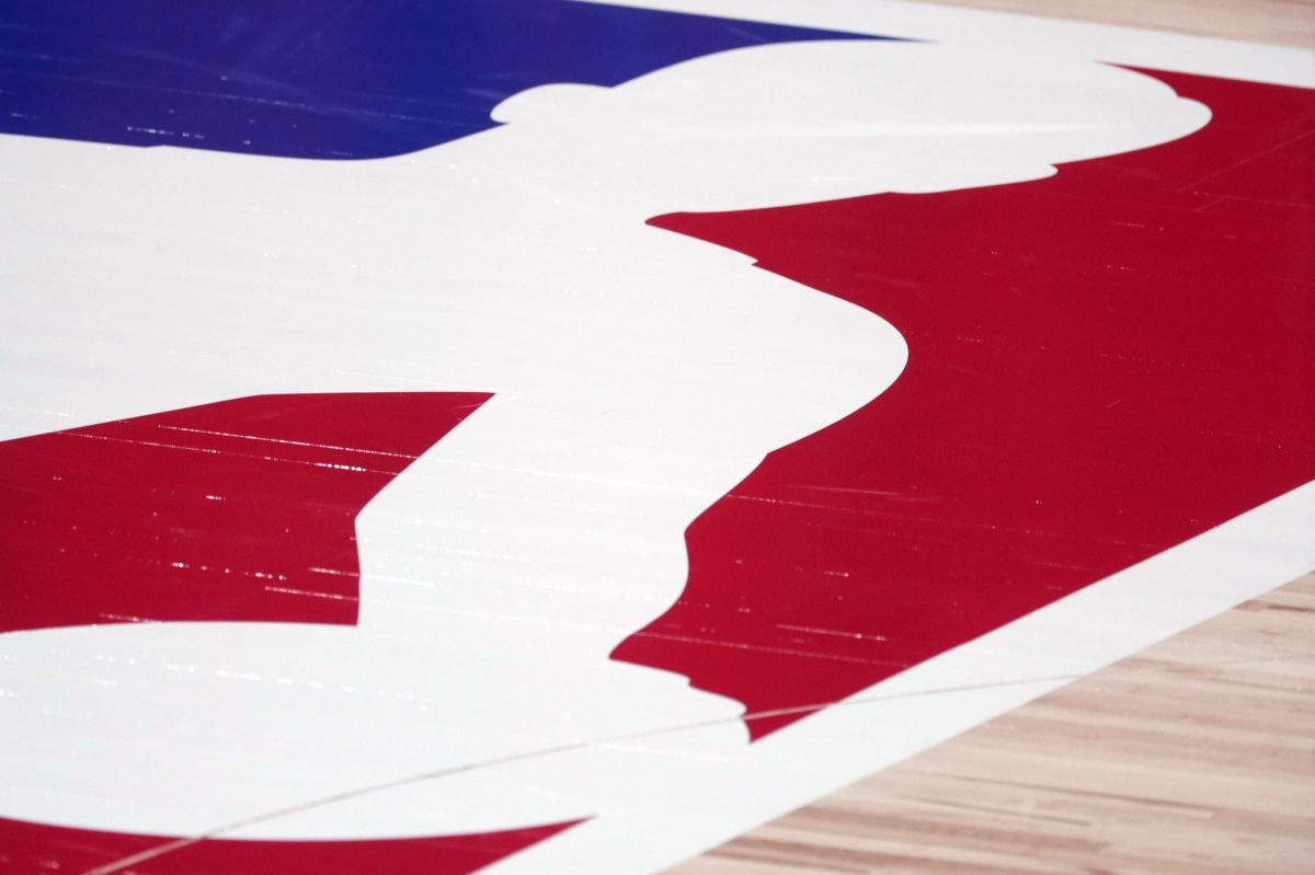 Closeup of the NBA logo on court before a playoff game. Unvaccinated players now face additional hurdles in certain cities if they want to play (including not being able to play in certain arenas)