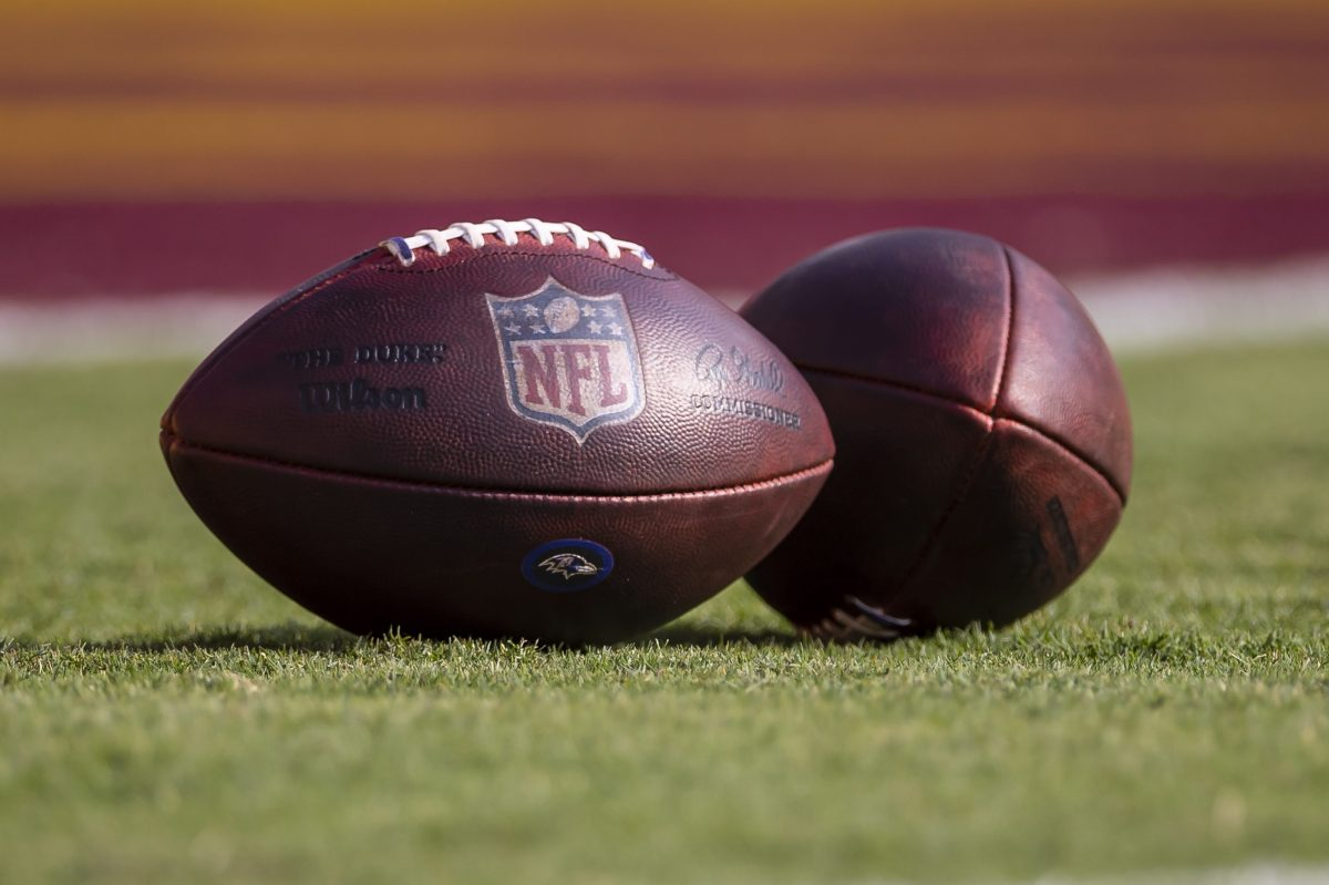 Two NFL footballs on the field before a 2021 preseason game