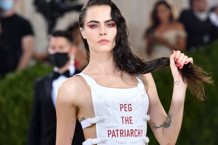 """Cara Delevingne wears a white vest with the words """"Peg the Patriarchy"""" at the 2021 Met Gala."""