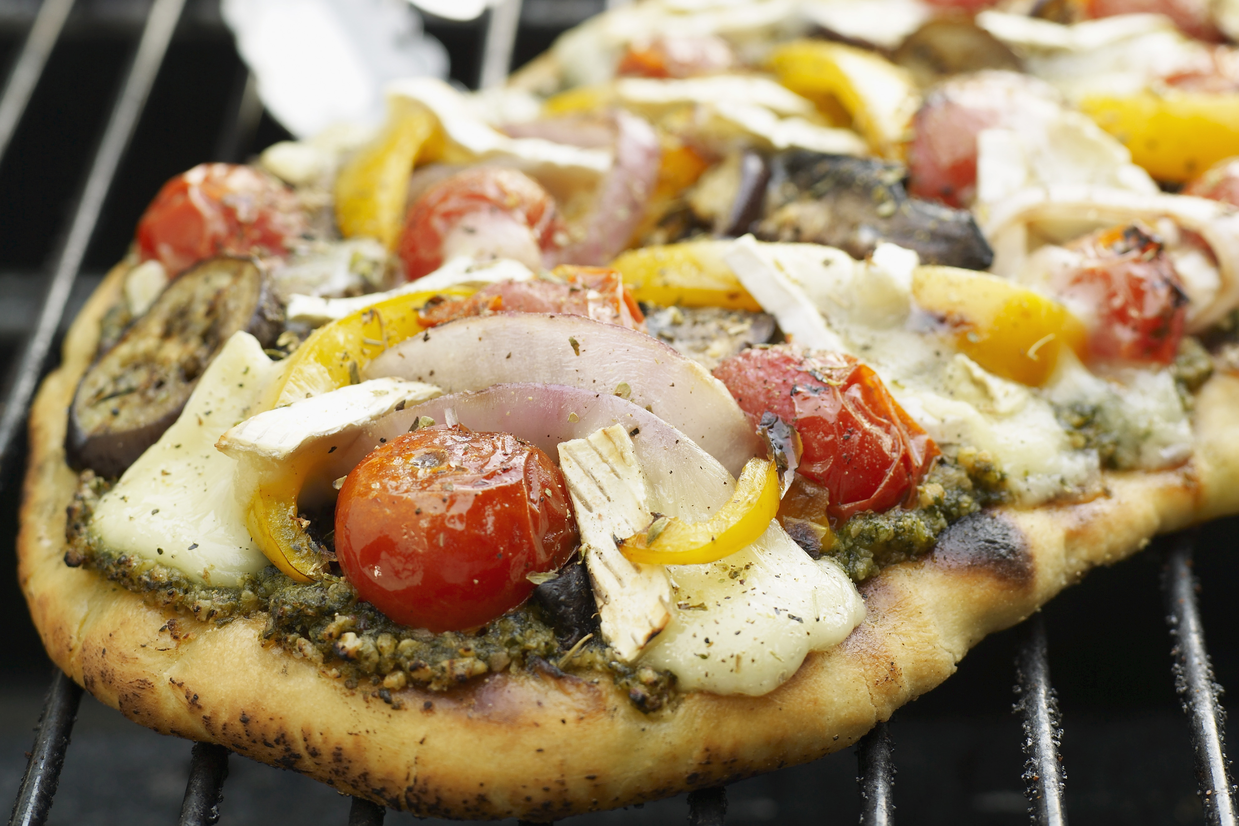 A pesto and vegetable pizza on the grill