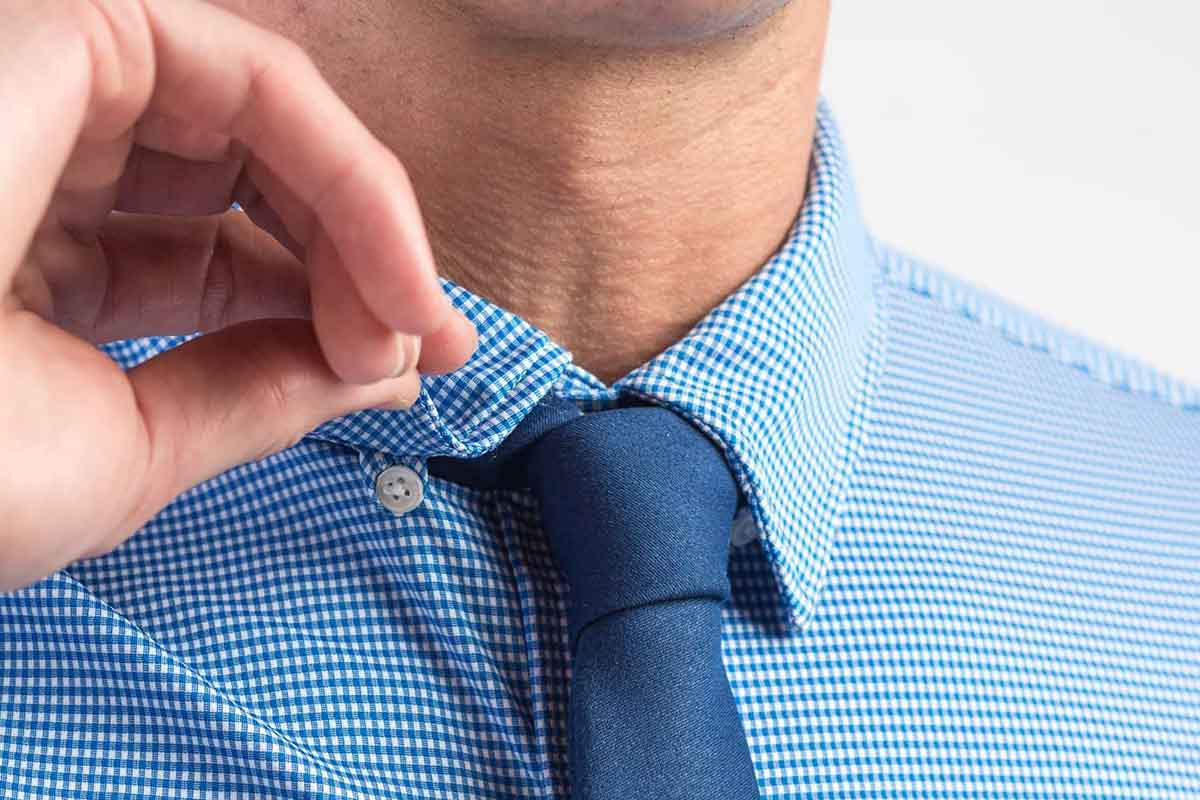 Man flipping up the collar of Rhone's Commuter Shirt, which is currently 50% off