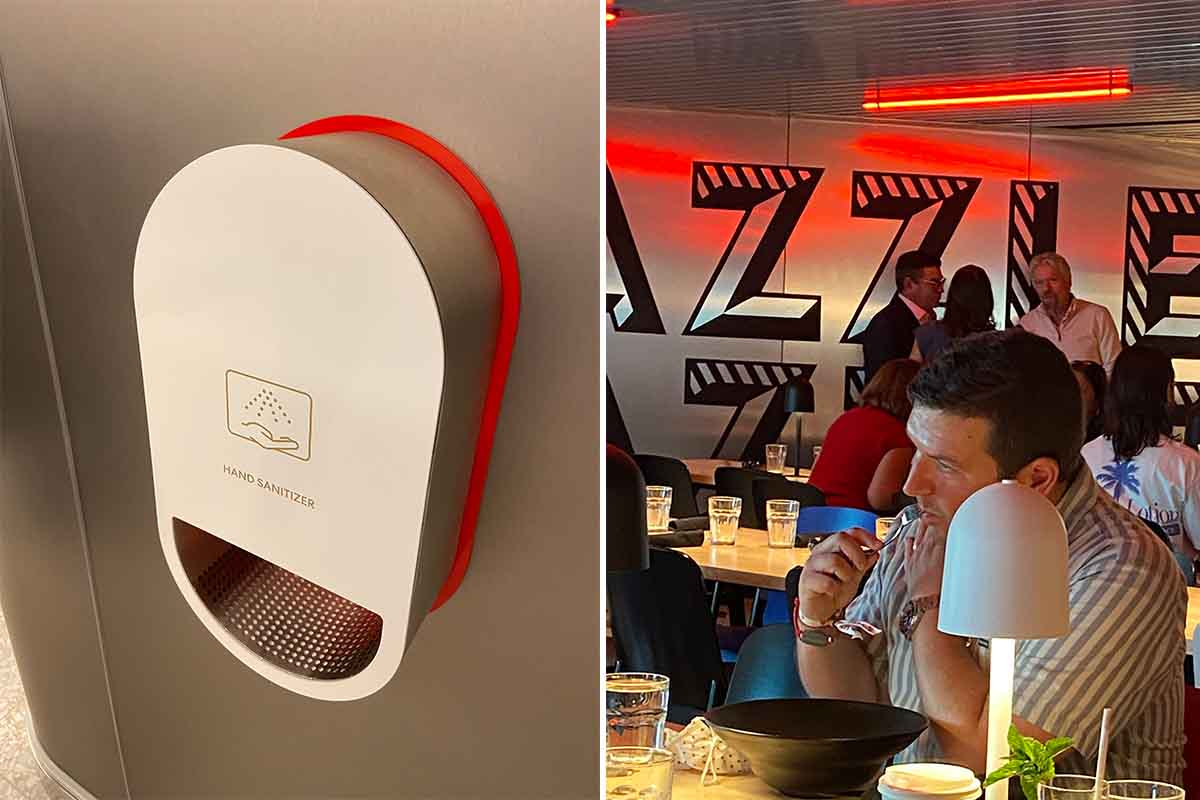 hand sanitizing station on left, Richard Branson in background at Razzle Dazzle restaurant on right on board the Scarlet Lady