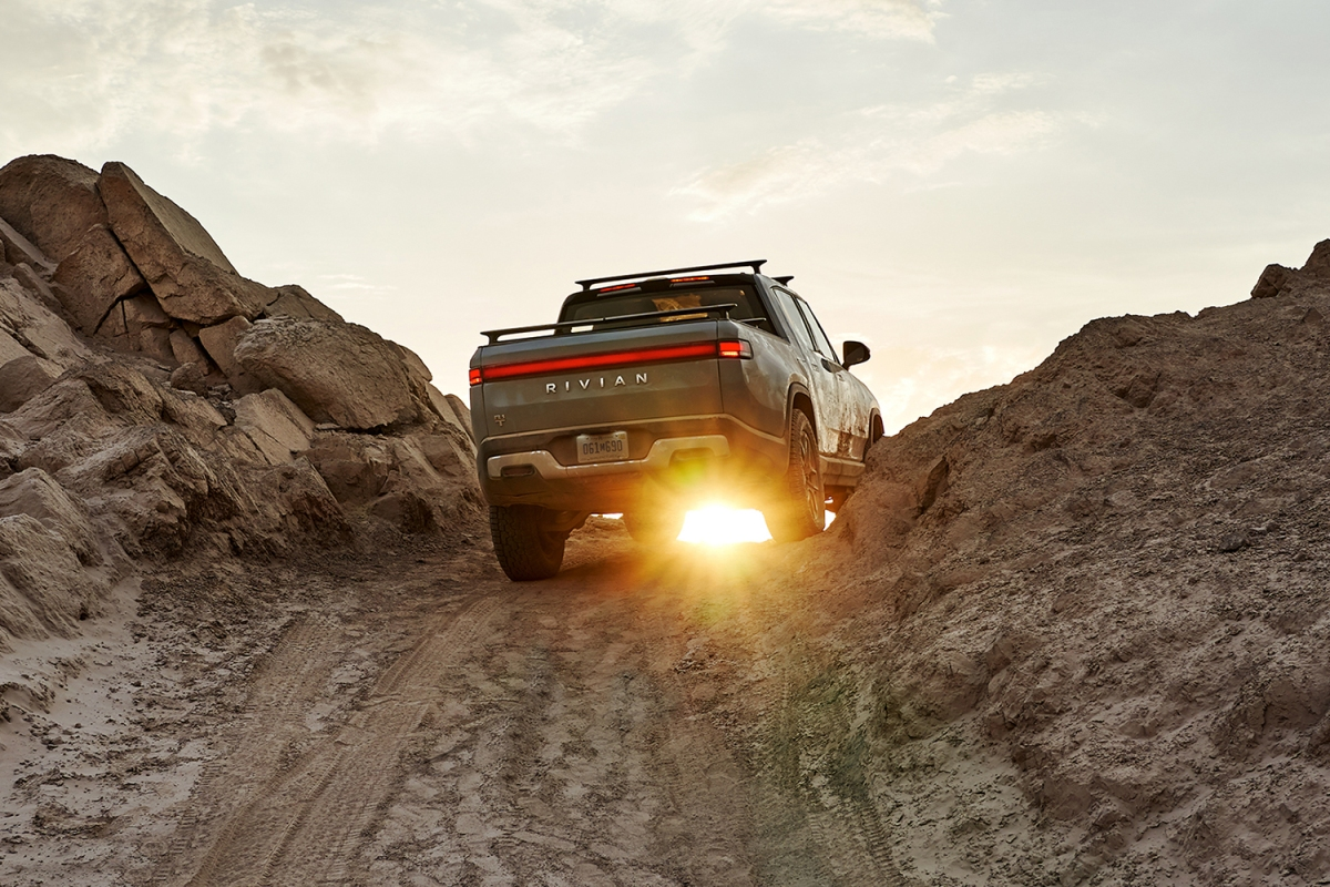 The Rivian R1T electric pickup truck shown from the rear driving over a rocky dirt hill at sunset