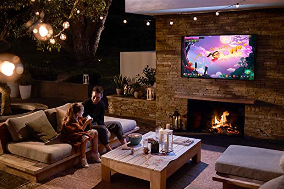 A father and daughter watching a Samsung Terrace TV outside