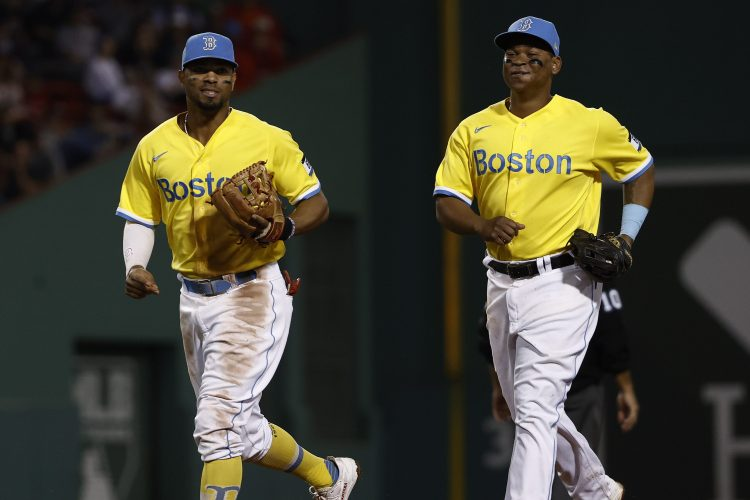 Rafael Devers and Xander Bogaerts of the Boston Red Sox share a laugh. The team is continuing to wear their yellow uniforms during a recent win streak.