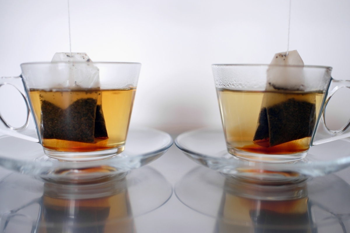 Image shows two tea bags steeping in clear mugs