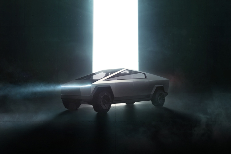 The Tesla electric Cybertruck from Elon Musk with its headlights on in front of a huge beam of light