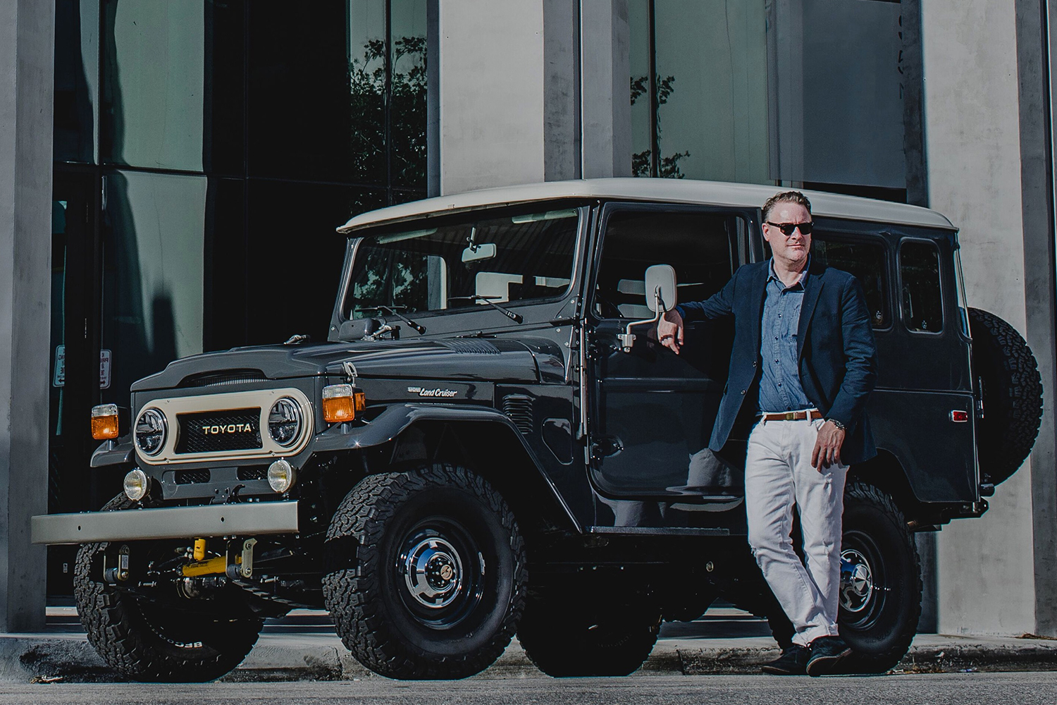 Menswear designer Todd Snyder in white pants and a blue jacket standing next to a custom Toyota Land Cruise designed in partnership with The FJ Company