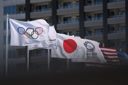 Olympic flags with the Olympic rings and Tokyo Olympics logo, as well as Japanese and American flags, are hoisted on flagpoles