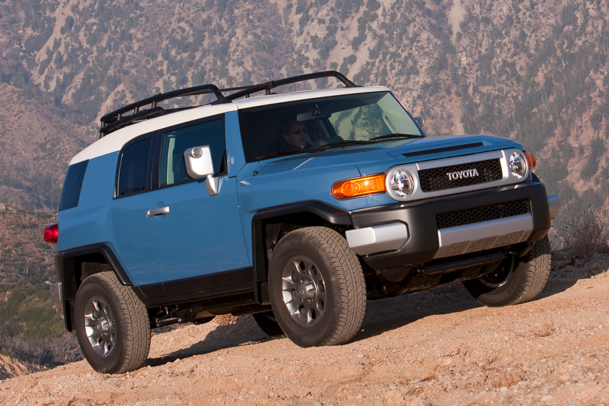 A blue Toyota FJ Cruiser driving up a rock face. The vintage off-road SUV is increasing in value in 2021, seven years after it was discontinued.