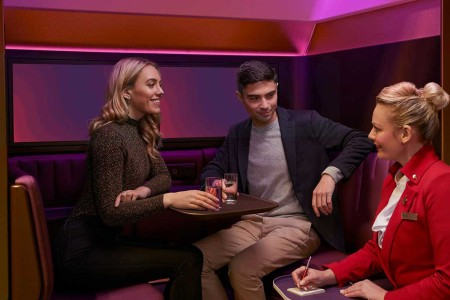 """Two passengers on Virgin Atlantic ordering drinks in """"The Booth,"""" a new immersive social space on some A350 aircraft"""