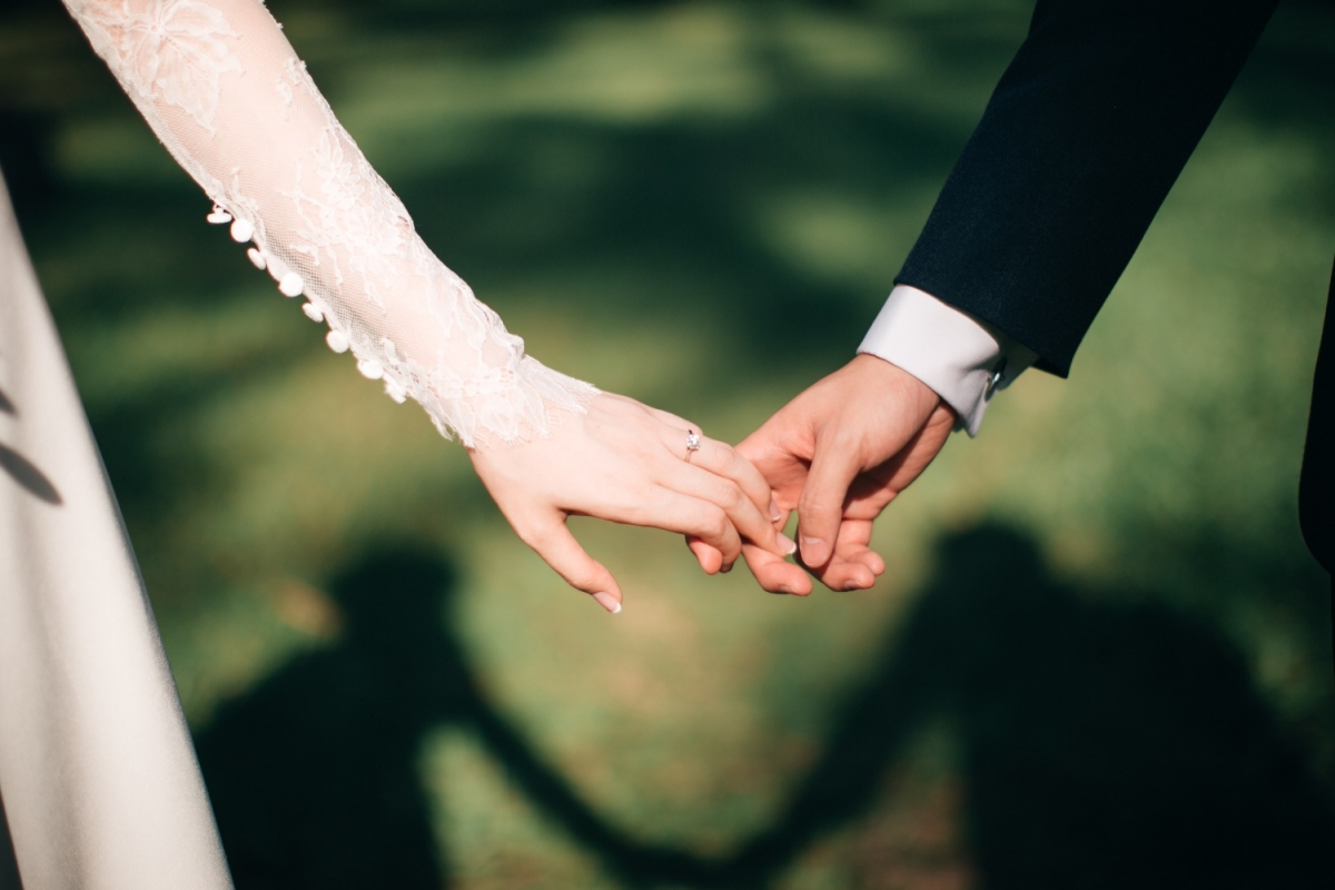 Photograph shows a bride and groom holding hands.