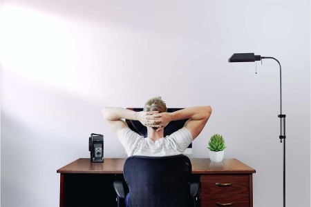 A man working from home and staring at his computer, arms locked behind his head. A new Microsoft study showed mixed results regarding WFH.