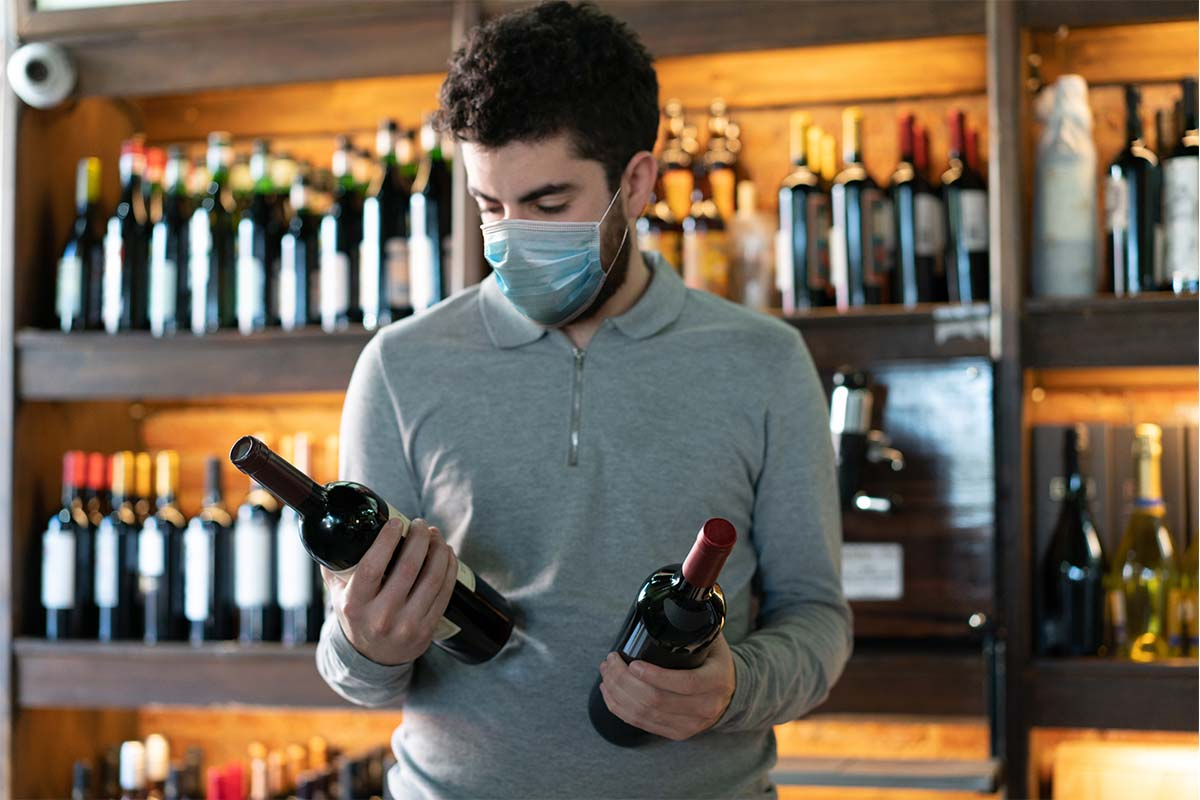 Young man at a wine cellar choosing between two wine bottles wearing a protective face mask. Covid-19 related supply issues are still affecting liquor stores in some states.
