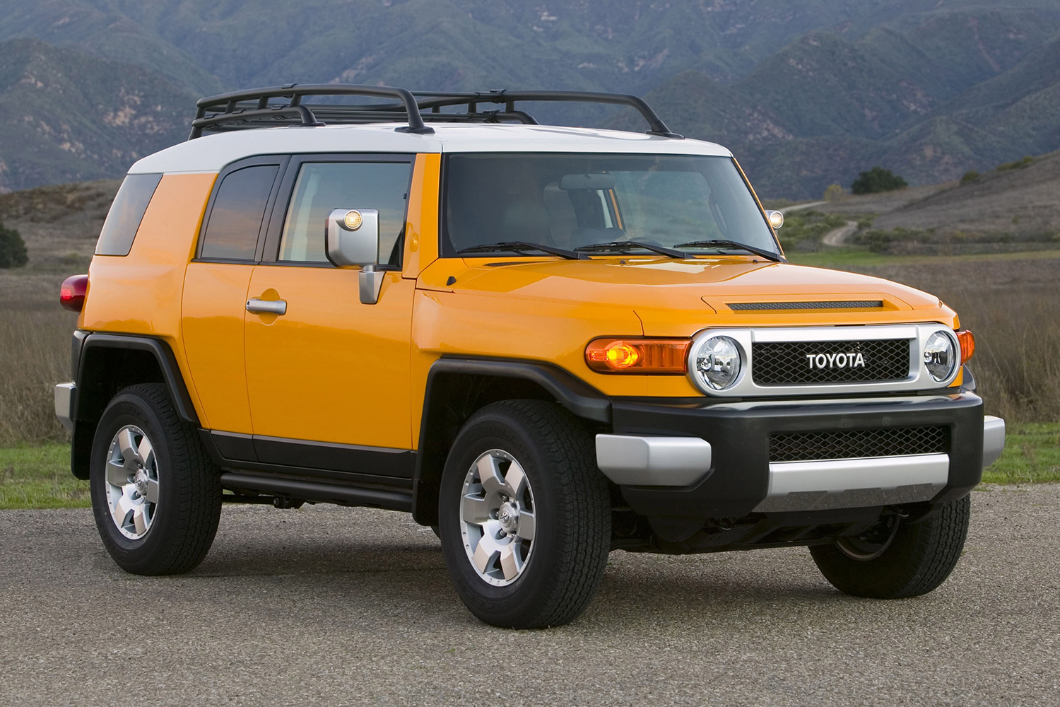 A yellow Toyota FJ Cruiser sitting still on the cement. The vintage off-road SUV was discontinued in 2014 but increasingly popular in 2021.