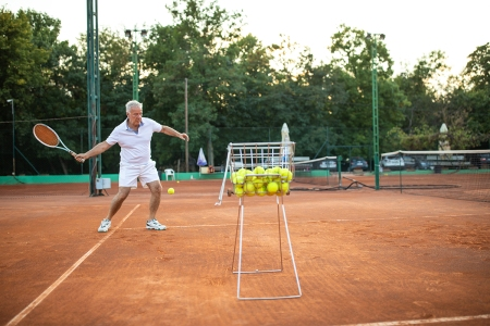An old man playing tennis on clay courts with a basket of tennis balls in the foreground