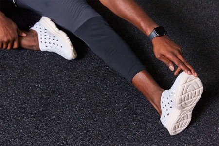 A man wearing recovery footwear stretches on a mat.